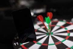 Phone stands on Darts field with Three Darts to hit red target close-up. Black mobile phone with blank screen stands on target close-up of Two red and one green stock photography