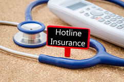 Phone and stethoscope with Hotline insurance. Royalty Free Stock Photos