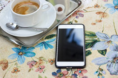 Phone on the tablecloth with flowers. Lace napkins and coffee Stock Image