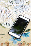 Phone on the tablecloth with flowers Royalty Free Stock Images