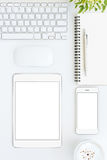 Phone and tablet blank screen on white table format vertical Stock Photography