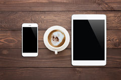 Phone tablet and coffee cup on wood table top view Stock Image