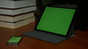Phone and tablet with green screen on the table in the office. Phone and tablet with green screen on the table