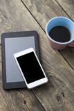 Phone and tablet pc on wooden desk Royalty Free Stock Images