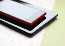 Phone and tablet. Red phone and black tablet computer Stock Photos