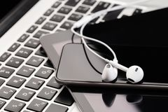 Phone and tablet with white headphones on laptop keyboard stock photo