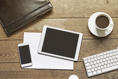 Phone and tablet on wooden workspace Stock Photography