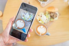 Phone take brunch picture. Hand hold phone take brunch picture with salad and coffee Stock Images