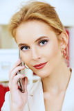 Phone talk. Pleasant business woman talking on the phone at the office and smiling Royalty Free Stock Images