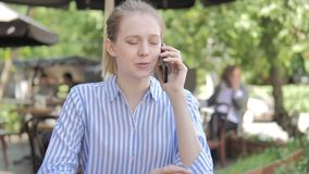 Phone Talk by Young Woman Sitting in Cafe Terrace stock video footage