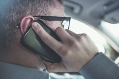 Phone Talking and Driving. Transportation Safety Concept. Caucasian Men Making Conversation by Cellphone While Driving the Car Stock Images