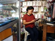 A phone technician works on a smartphone in her store in Antipolo City. ANTIPOLO CITY, PHILIPPINES - APRIL 24, 2017: A phone technician works on a smartphone in royalty free stock image