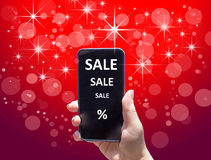 The phone with text SALE in female hand on the red background Stock Photography
