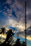 Phone tower antenna technician. Silhouette Photo of Phone tower antenna technician are doing to repair a slings cable Royalty Free Stock Image