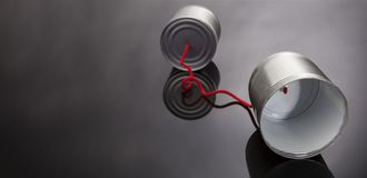 Free Phone Toy From A Tin Can Lying On A Smooth Black Polished Table Stock Photo - 120834380