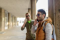On the Phone. Two young men talking on the phone in city passage Royalty Free Stock Image