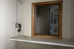 Phone used by visitors at abandoned prison. Phone next to window used by visitors to prison to communicate with inmates behind glass royalty free stock image
