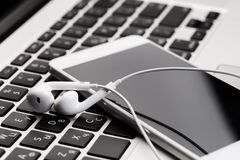 Phone with white headphones on laptop keyboard royalty free stock photo