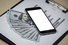 The phone with a white screen is on dollars with sheets with cha. Rts. Template stock photo