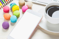 Phone white screens, keyboards and macaroons, coffee cup on the table Royalty Free Stock Photography