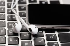 Free Phone With White Headphones On Laptop Keyboard Royalty Free Stock Images - 139019719
