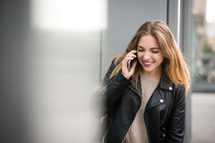 On phone - woman talking with friend Stock Photo