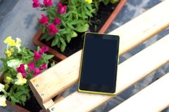 Phone on a wooden table, around the flowers Royalty Free Stock Image