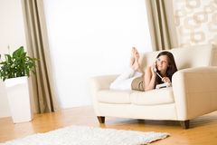 On the phone: young woman calling in lounge Royalty Free Stock Photography