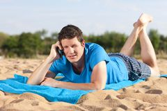 Phonecall on the beach. Young man with mobile phone lying on the beach Stock Images