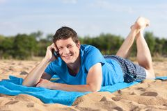Phonecall on the beach. Young man with mobile phone lying on the beach Stock Photography