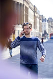 Phonecall in the city. Man on the phone in the City. He is walking down the highstreet with his sunglasses on his head Royalty Free Stock Photography