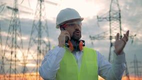 Phonecall de un especialista de sexo masculino que se coloca al lado de líneas de electricidad almacen de video