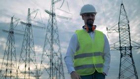 Phonecall des männlichen Technikers bei der Stellung neben Linien der elektrischen Energieübertragung stock video