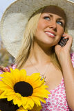 Phonecall and Flowers. A beautiful young blond woman carrying a basket of sunflowers and talking on her mobile phone Royalty Free Stock Photography