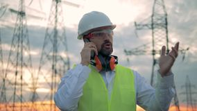 Phonecall of a male specialist standing beside electricity lines. HD stock video