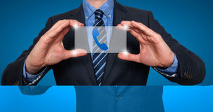 Phonel和联络标志在商人前面 免版税库存图片
