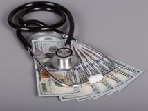 Phonendoscope για τη διάγνωση και τα χρήματα, σε γκρίζο Στοκ φωτογραφία με δικαίωμα ελεύθερης χρήσης
