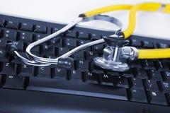Phonendoscope and black keyboard Stock Image