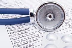 Phonendoscope of de stethoscoop met stuk van de chroom het grote borst op de kant en de tabletten of capsules in een grijs blaarp royalty-vrije stock foto