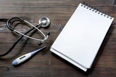 Phonendoscope, el termómetro y el cuaderno en la visión de escritorio de madera oscura conciertan una cita con mofa del doctor pa Fotos de archivo
