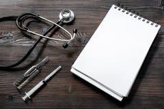 Phonendoscope, la jeringuilla, la ampolla y el cuaderno en la visión de escritorio de madera oscura conciertan una cita con mofa  Imagen de archivo libre de regalías