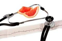 Phonendoscope och cardiogram med grapefrukten royaltyfri foto