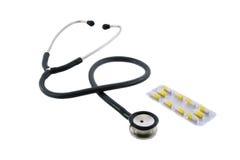 Phonendoscope and pills. Isolated on white background Stock Photos