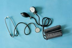 Phonendoscope stethoscope and sphygmomanometer on blue background. stock image