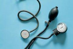 Phonendoscope stethoscope and sphygmomanometer on blue background. royalty free stock photography