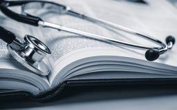 Phonendoscope sul libro di medicina immagini stock