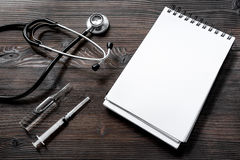 Phonendoscope, syringe, ampoule and notebook on dark wooden desk top view make an appointment with doctor mock up Royalty Free Stock Image
