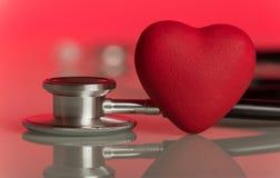 Phonendoscope y corazón artificial, en rosa foto de archivo