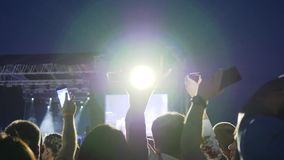 Phones in raised hands crowds on background stage lights, people on concert waving hand with mobiles stock video footage