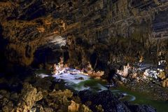 Phong Nha Ke national park / Vietnam, 16/11/2017: Group of cavers passing an underground river and huge rocks inside the giant royalty free stock image